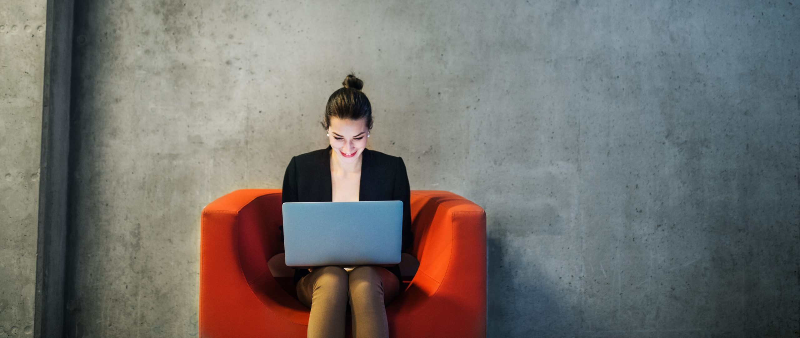 A young businesswoman with laptop sitting on red armchair in office